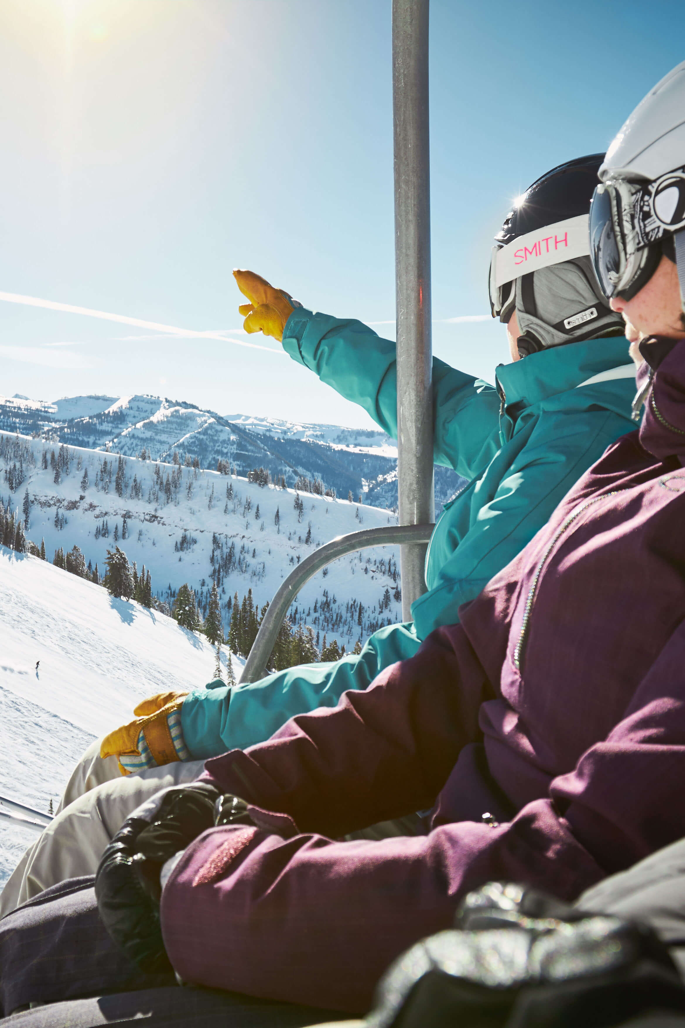 Skiers pointing at mountain from chair lift