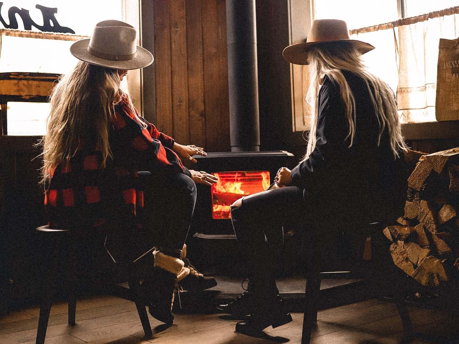 women sitting at a fire