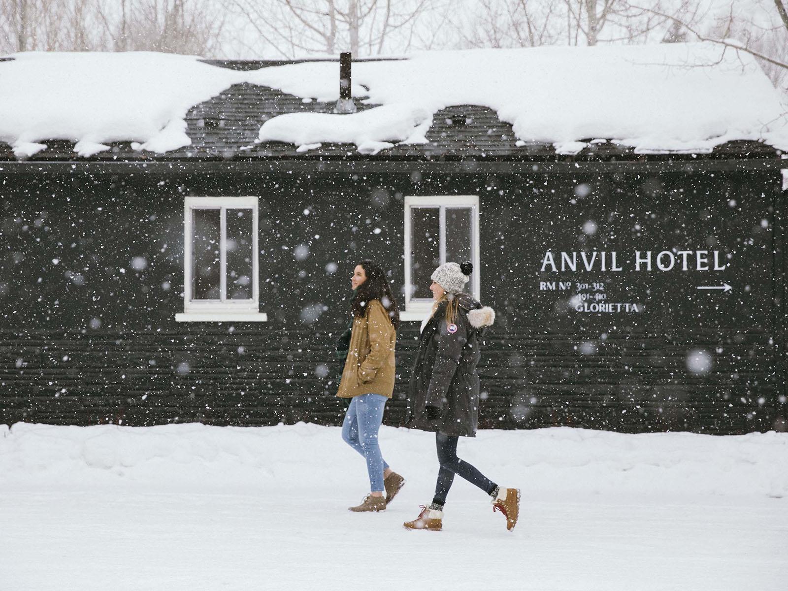 Ladies walking in snow in front of Anvil Hotel